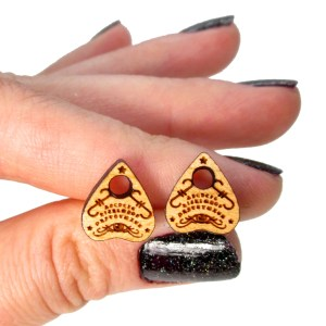 hand holding spirit board planchette shape stud earrings to show size