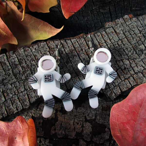 astronaut earrings on wood background