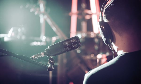 Person with headphones and Studio microphone close-up, in a recording Studio or concert hall, with a drum set on the background in out-of-focus mode. Beautiful blurred background of colored lanterns