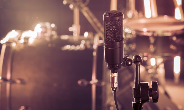 The microphone in a recording Studio or a concert hall close up of drum kit and an acoustic guitar in the background. Beautiful blurred background of colored lanterns. Musical concept in vintage style