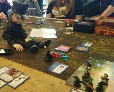 Parker rolling a dice beside a Super Dungeon Explore Tile