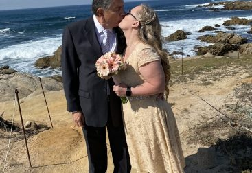 A man in a dark suit is kissing a woman in an ivory dress. She is holding flowers. They are in front of an ocean.