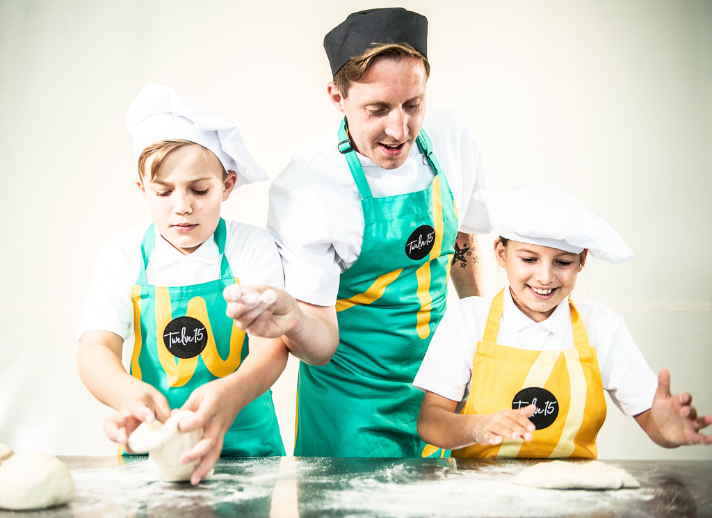 A staff member helps two children make pizza dough.