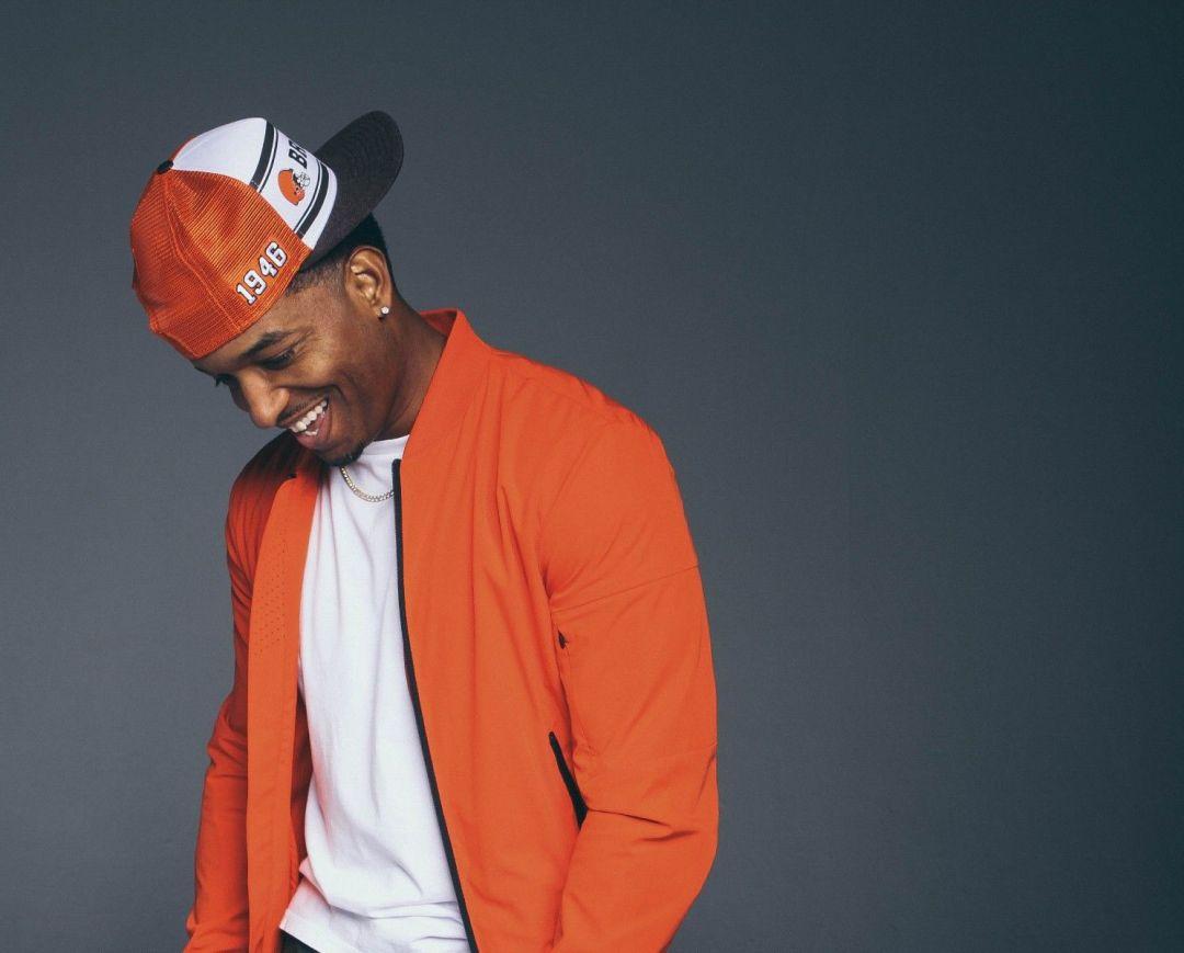 Portrait of Jc smiling, wearing orange