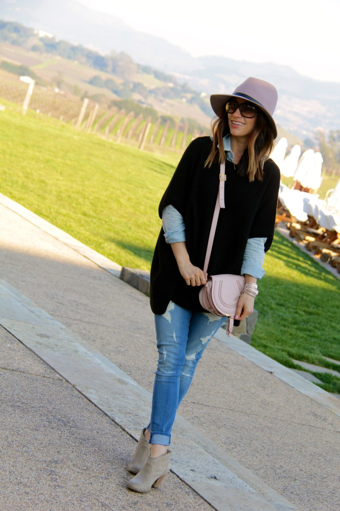 distressed denim, pink fedora, black poncho