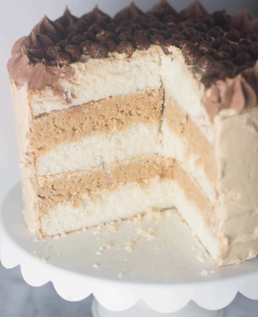 Vanilla Bean Peanut Butter Crunch Cake--vanilla cake topped with peanut butter frosting, filled with rice krispies, white chocolate, and (yes) peanut butter