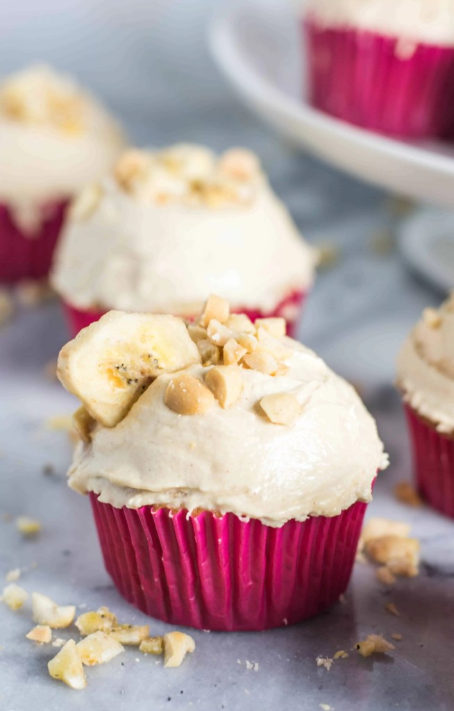 cupcake with frosting and a banana chip with more banana cupcakes in the background
