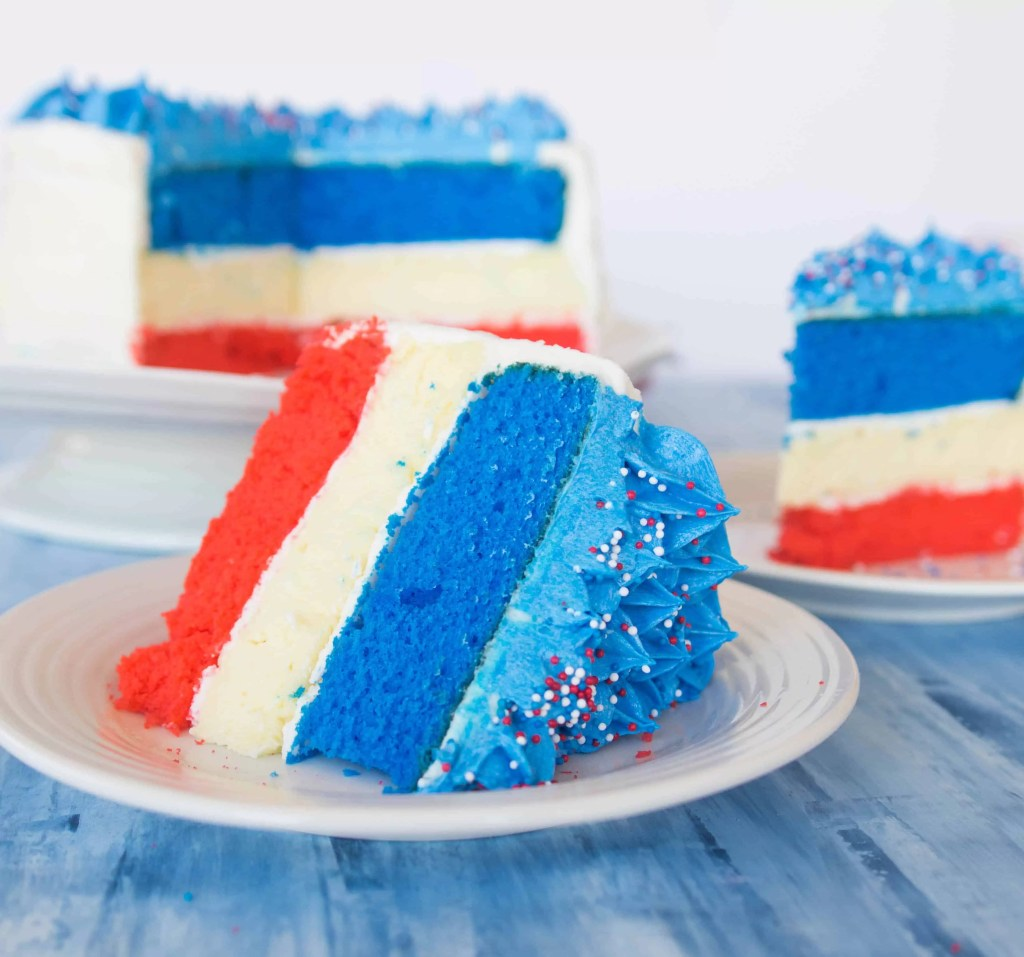 slice of Fourth of July cheesecake cake sitting on a plate with the rest of the cake in the background