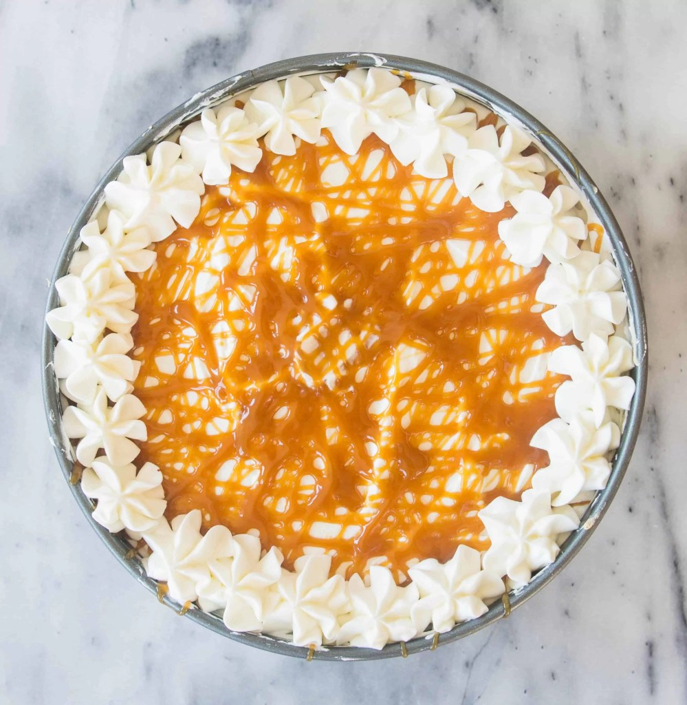 overhead photo of no-bake caramel macchiato cheesecake with caramel drizzled over the top and whipped cream piped around the edge