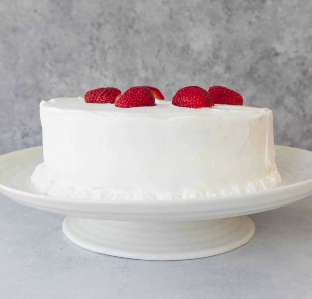 strawberry shortcake layer cake decorated with fresh strawberries sitting on a cake stand