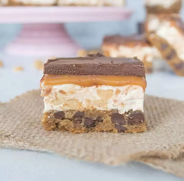Chocolate chip cookie Snickers bars are a delicious hybrid of the classic cookie and delicious candy bar.  You need these in your life! recipe via itsybitsykitchen.com #cookies #chocolate #cookiebars