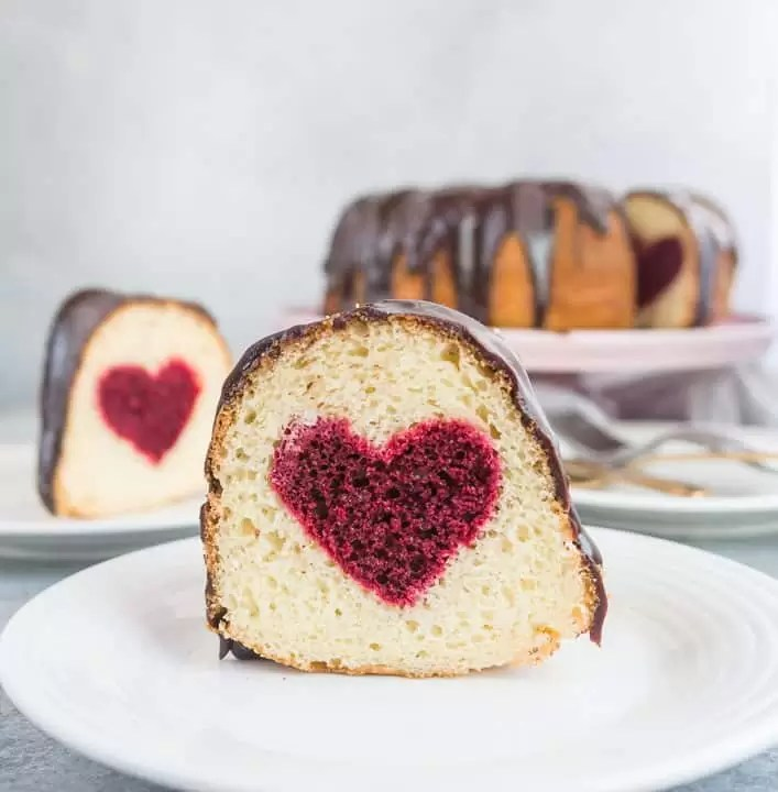 slice of hidden heart bundt cake on a plate with the rest of the cake in the background.