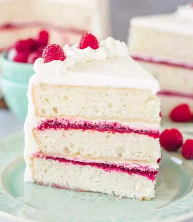 slice of white chocolate raspberry cake sitting on a plate with a bowl of raspberries behind it