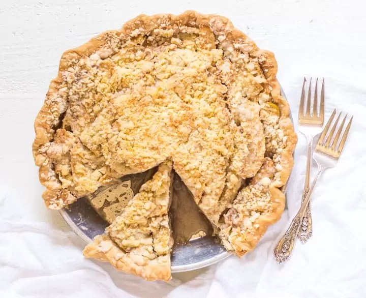 overhead photo of sliced cheddar apple pie next to two forks