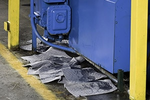 disposable pig oil absorbents in use at a manufacturing plant