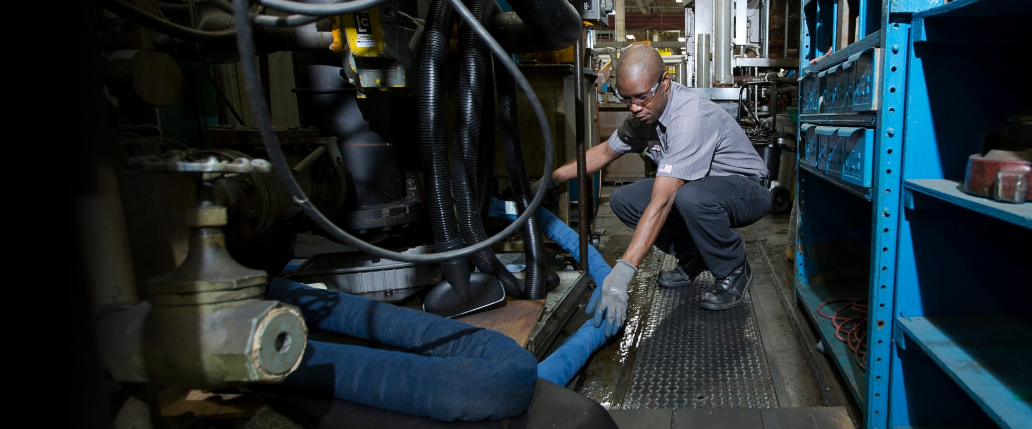 SorbIts reusable oil absorbent socks being placed under a machine to soak up leaking oil