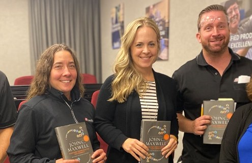 ITU Absorbtech book club participants hold up a John C. Maxwell book
