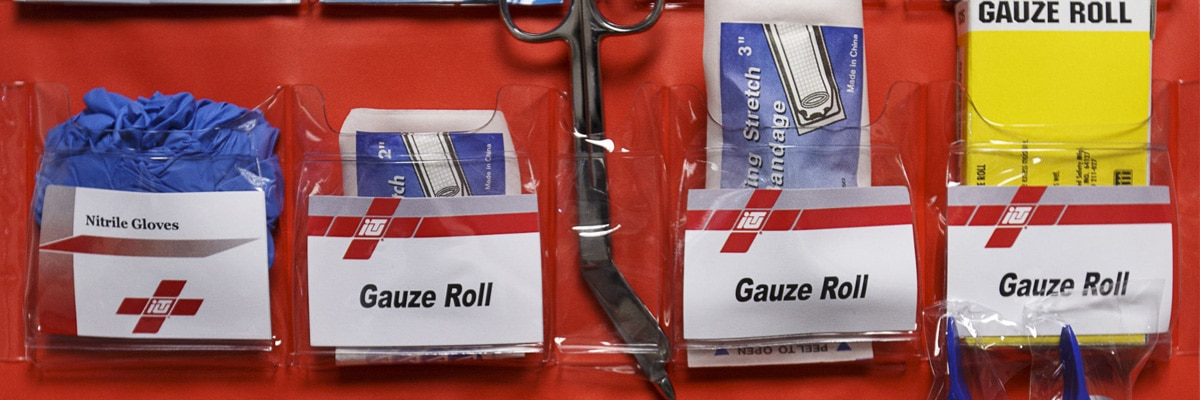 First Aid Cabinet Kit in the Workplace with Gloves, Gauze Rolls, Tweezers, and Scissors
