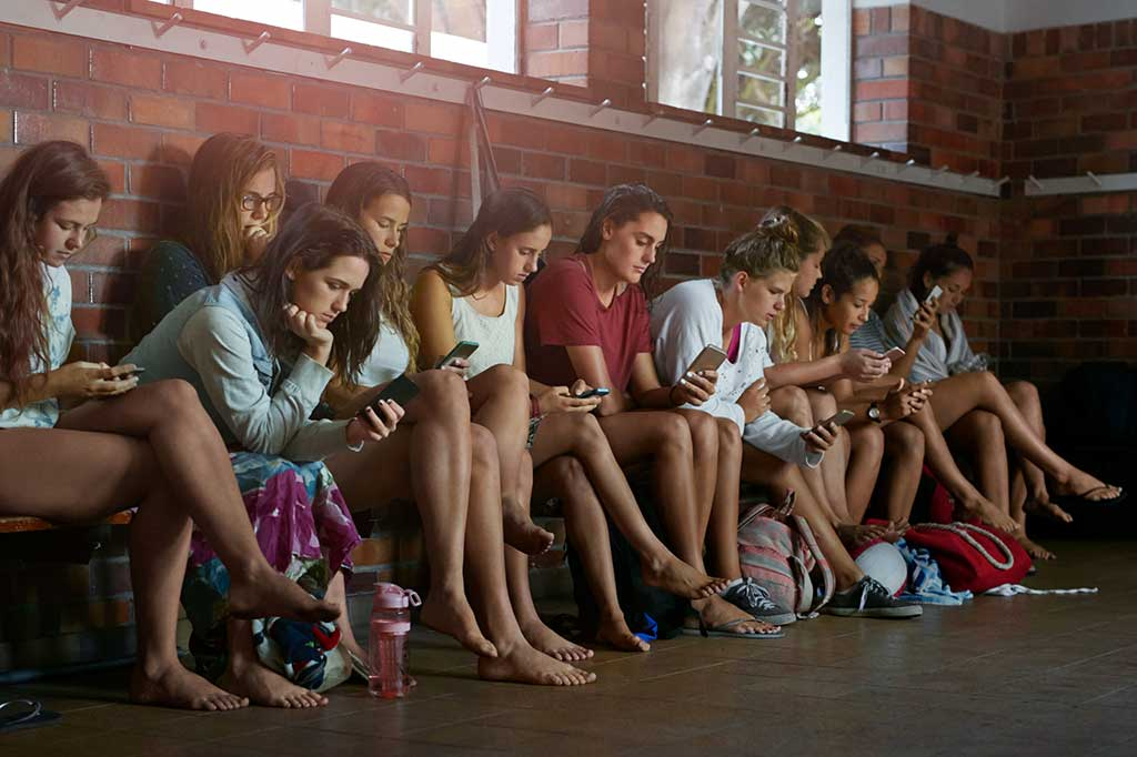 Adolescentes peruanos chequean su celular antes de levantarse de la cama