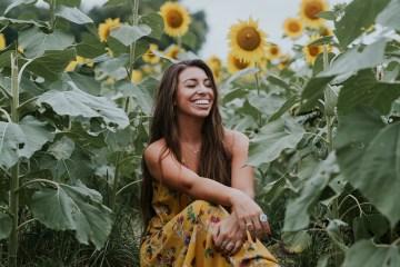 Woman sitting in a sunflower garden by Brooke Cagle via Unsplash