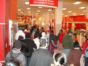 Shoppers flood into Target on Black Friday. Retail stores are opening earlier and earlier on the holiday every year. Some will even stay open on Thanksgiving this year.  Photo via/Wikimedia Commons