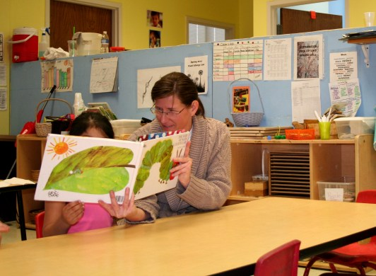 Kim Cooper, Teacher's Assistant at IU South Bend's Child Development Center, reading to children after lunchtime. (Preface Photo/Izza Jatala)