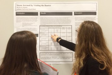 Michaela Kapala, right, refers to the results of her research into the stress accrued by visiting the dentist Friday, April 17, 2015. (Photo/Bri Schmitt).