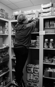 PHOTO CREDIT: LEAH FICK CAPTION: Senior, Deanna Bernal reaches for items in Titans Feeding Titans food pantry.