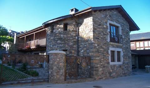 Fachada, torreón y balconada en casa unifamiliar de piedra