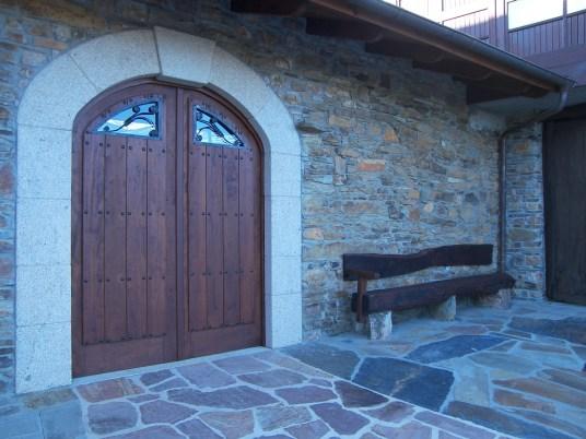Puerta de madera y banco-traviesa en casa de piedra