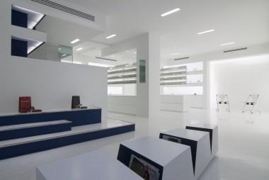 Vista general óptica en planta inferior con mesa revistero y expositores de gafas-producto