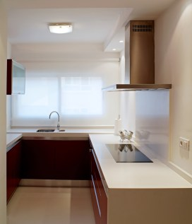 Diseño interior de piso en Galicia. Mesado de trabajo, vitrocerámica y fregadero al fondo