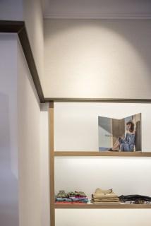 Remates superiores con perfiles metálicos lacados efecto latón en diseño interior de tienda de moda de mujer Jonathans