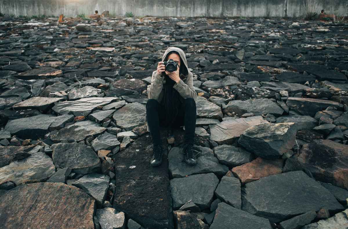 concentrated photographer taking picture on stones
