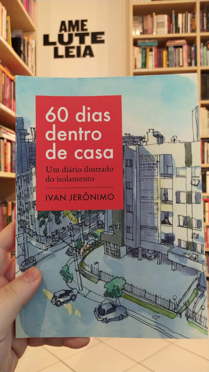 """Livro """"60 dias dentro de casa"""" segurado por uma mão, com as estantes ao fundo e letreiro na parede onde se lê """"Ame, lute, leia"""""""