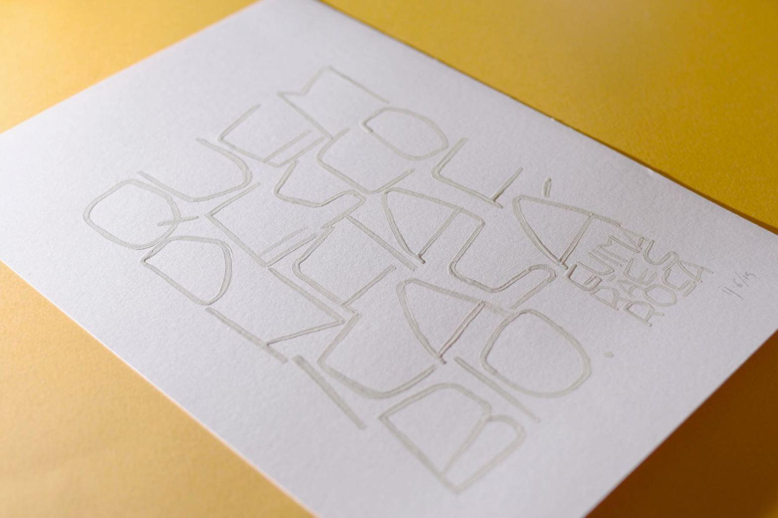 Trabalho de caligrafia com letras maiúsculas a pincel, em tinta guache branca sobre papel branco