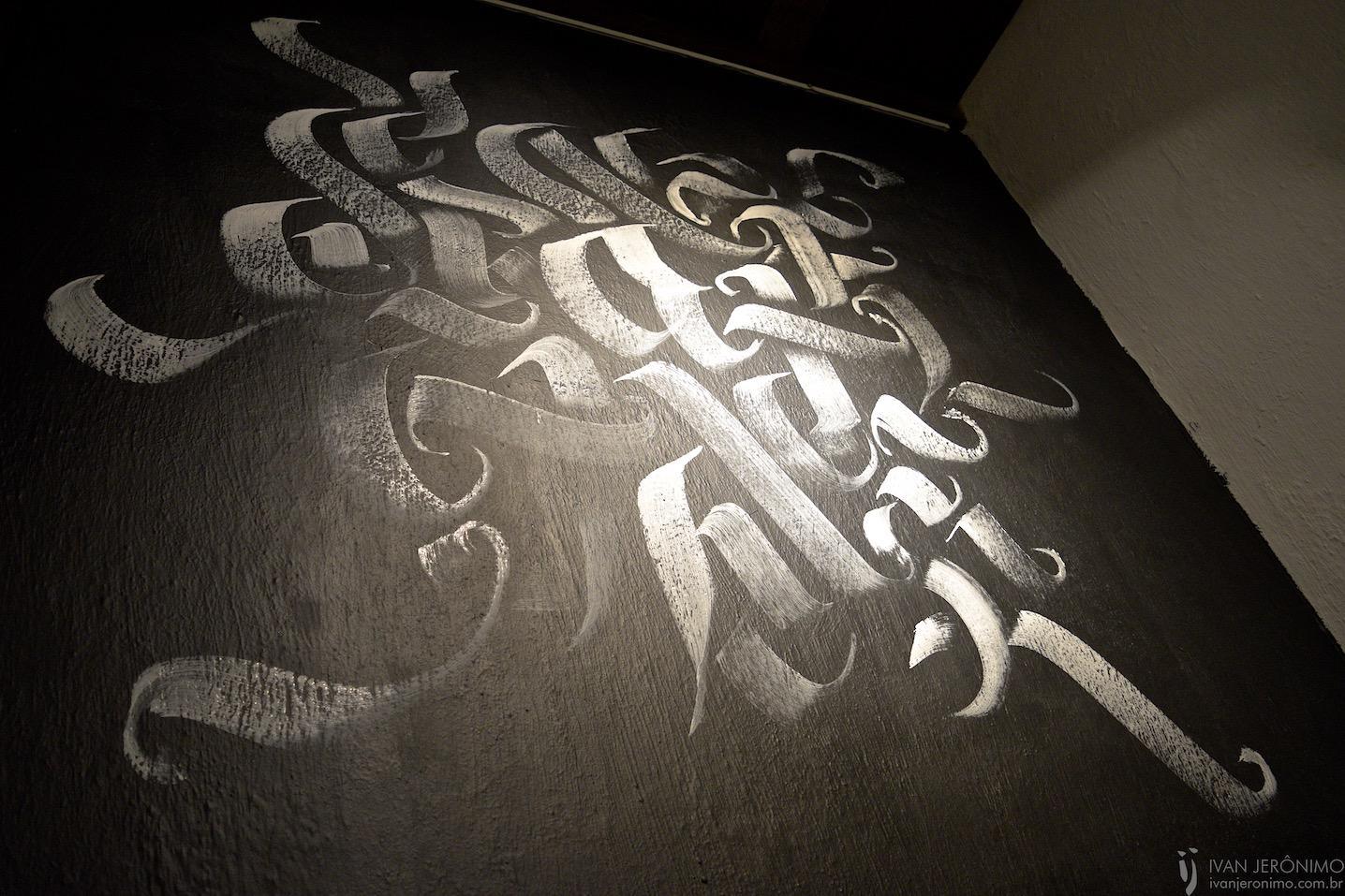 caligrafia abstrata em branco sobre parede preta do Sítio, na Lagoa da Conceição