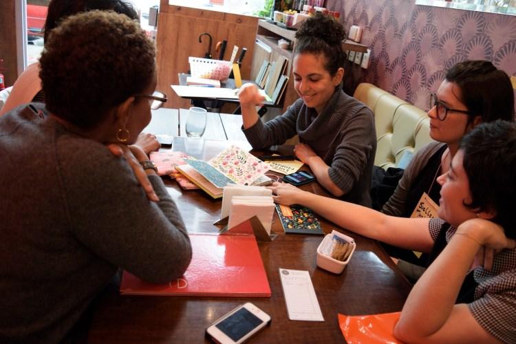 Mesa do café com participantes examinando trabalhos