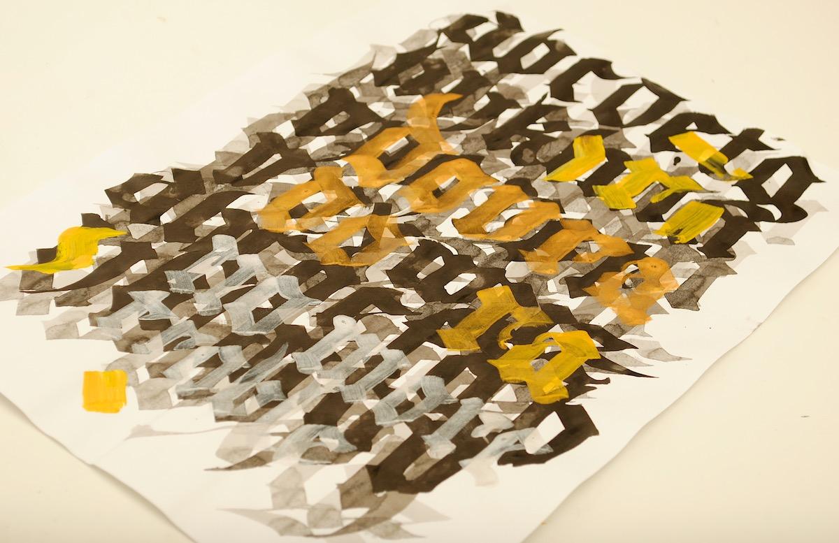 Trabalho de caligrafia com letras góticas em cinza, preto e dourado justapostas