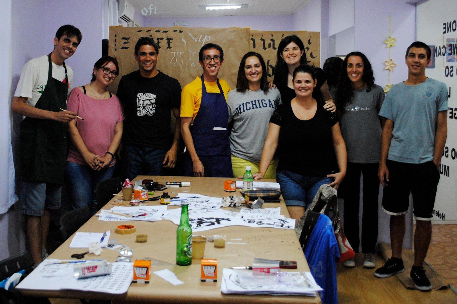 Foto com oito participantes da oficina Caligrafia Livre na sala do Simbiose Coworking