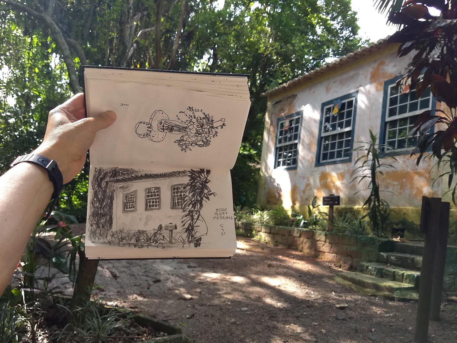Foto da casa de arquitetura açoriana com autor segurando caderno com o desenho em frente