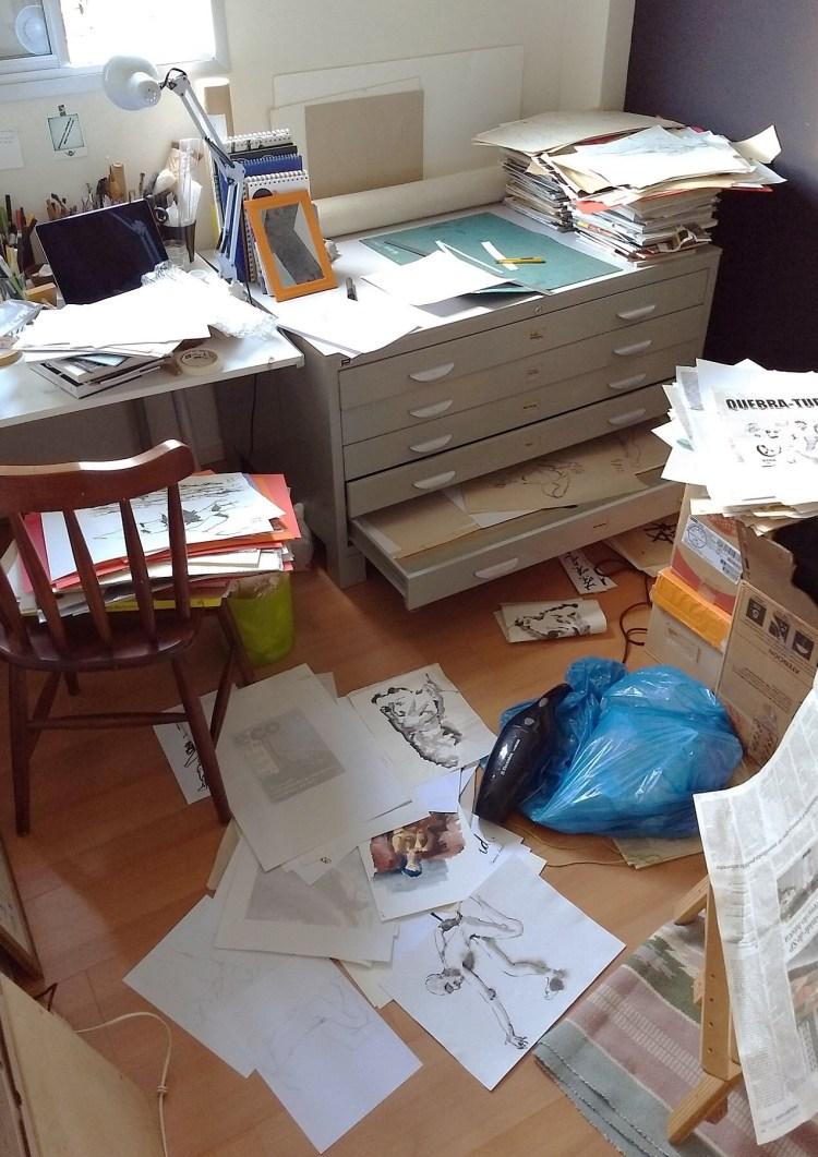 Ateliê com a mapoteca aberta e os papéis espalhados