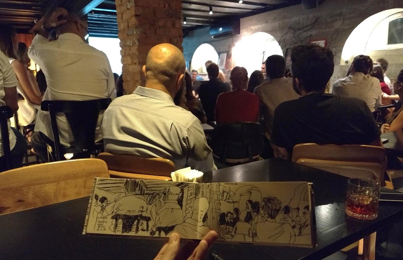 Público do evento no Porão, virado para os palestrantes. Em primeiro plano, caderno horizontal aberto com o desenho