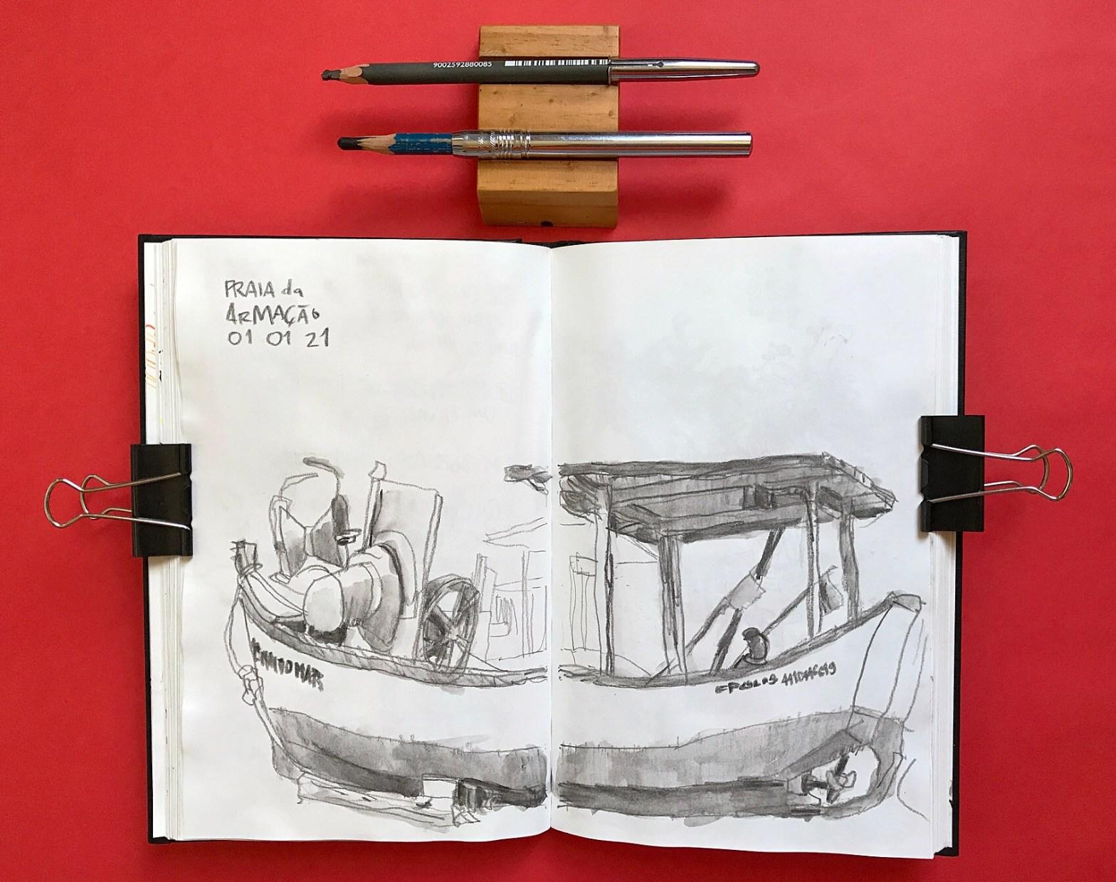 Foto de caderno aberto com desenho em página dupla de um barco de pesca. Acima do caderno, dois lápis.
