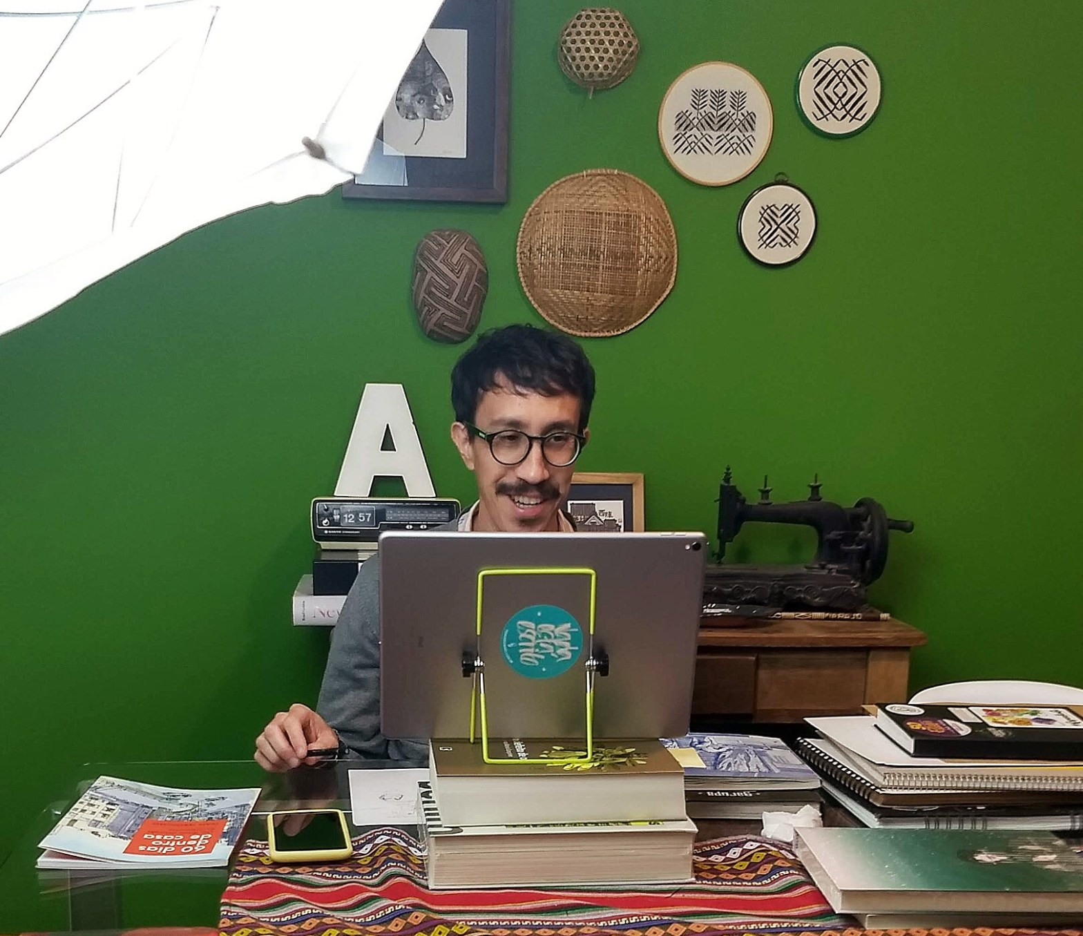 Foto do autor sentado em uma mesa, em frente a um tablet, cercado por cadernos, com uma parede verde ao fundo, onde estão pendurados bordados e objetos indígenas