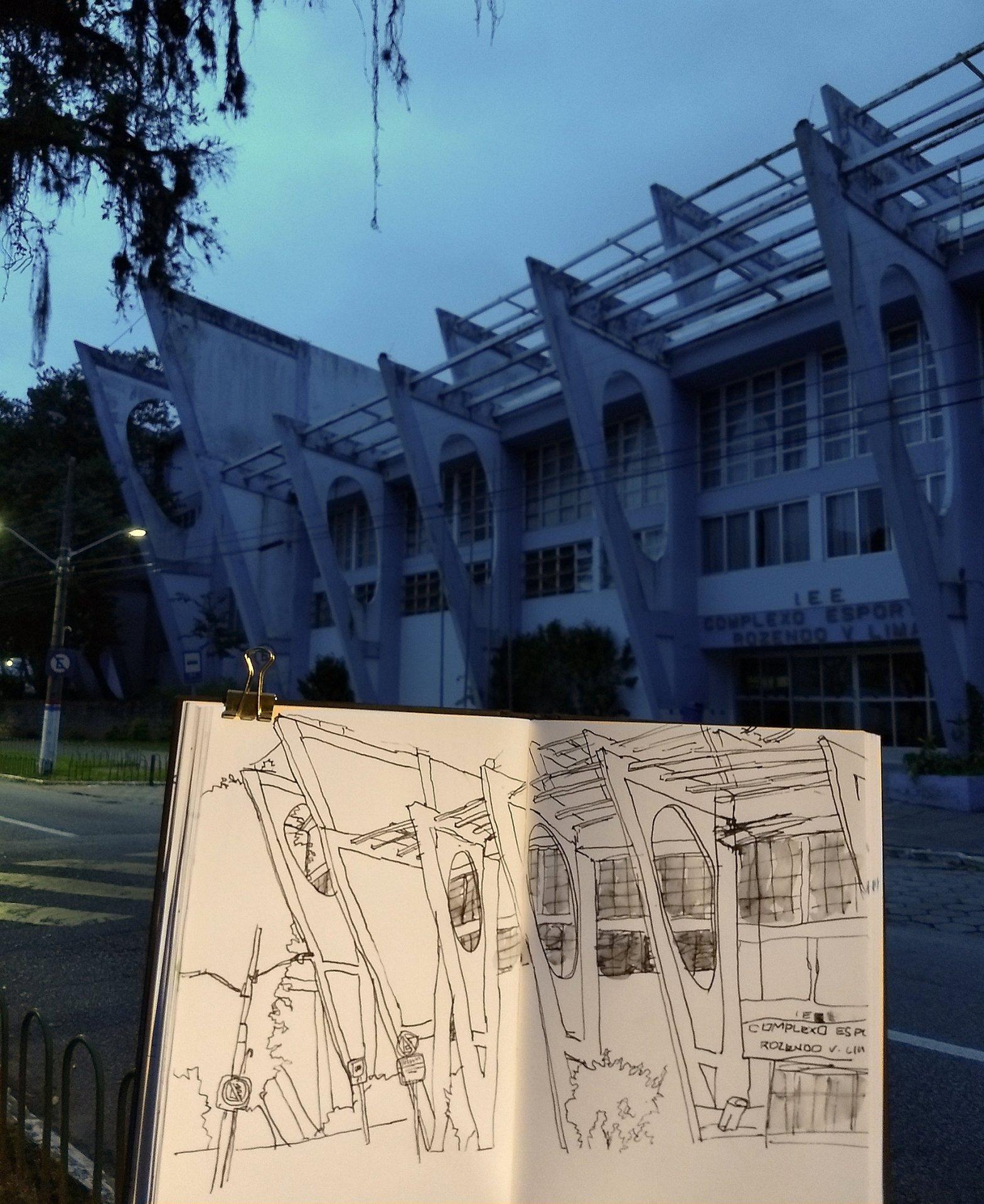 Em primeiro plano, caderno com desenho da fachada do ginásio. Ao fundo, o ginásio verdadeiro, com as colunas triangulares