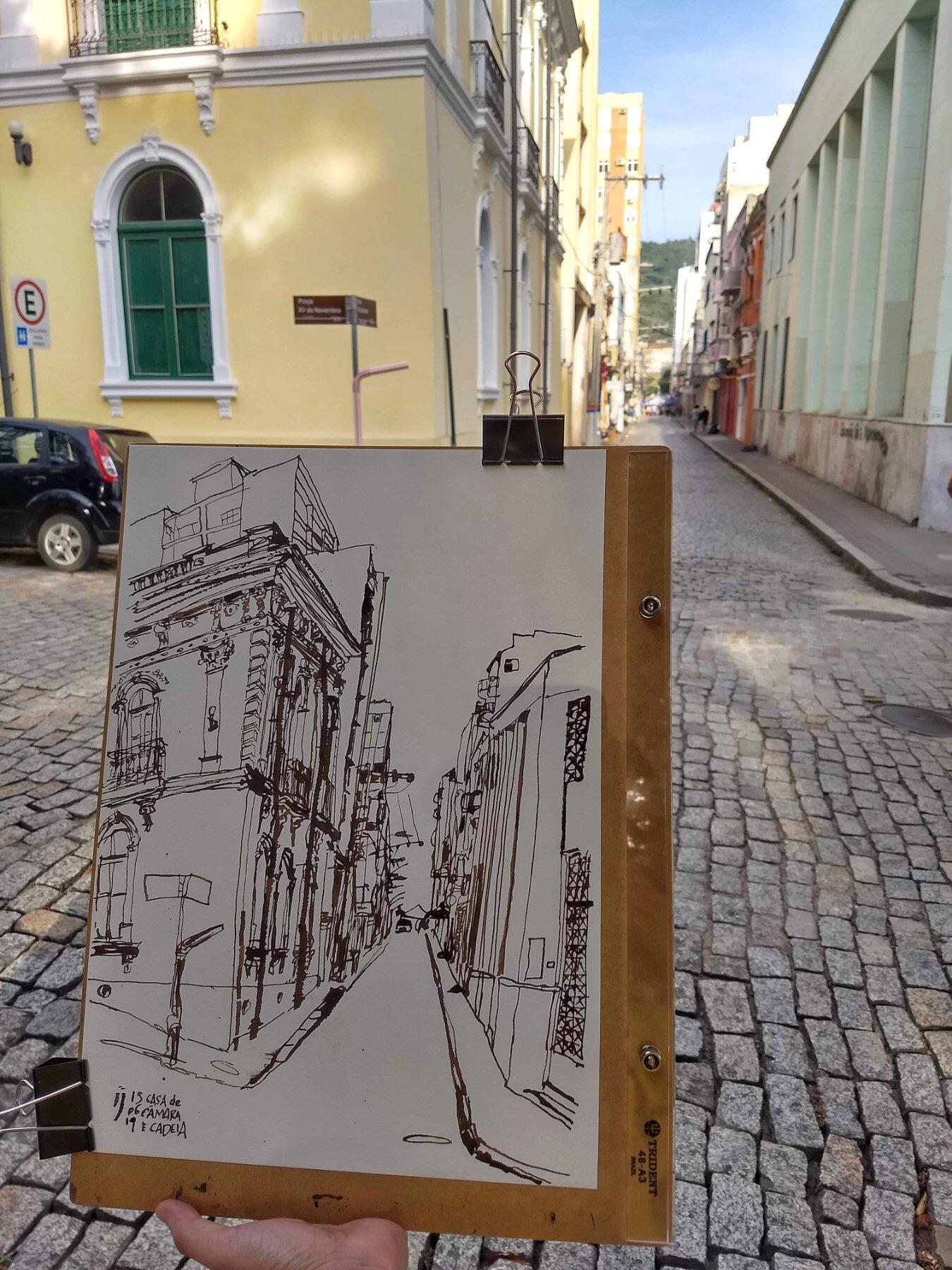 Mão segura desenho com os dois prédios nas esquinas em segundo plano