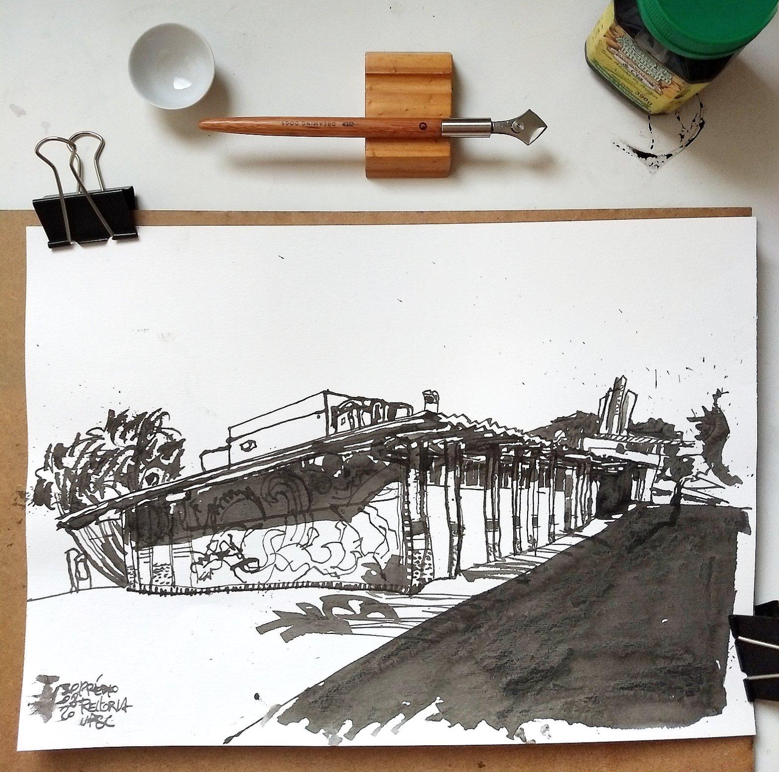 Vista de cima de uma mesa com o desenho do prédio da reitoria, uma pequena vasilha branca, um tira linhas e um pote com tinta preta