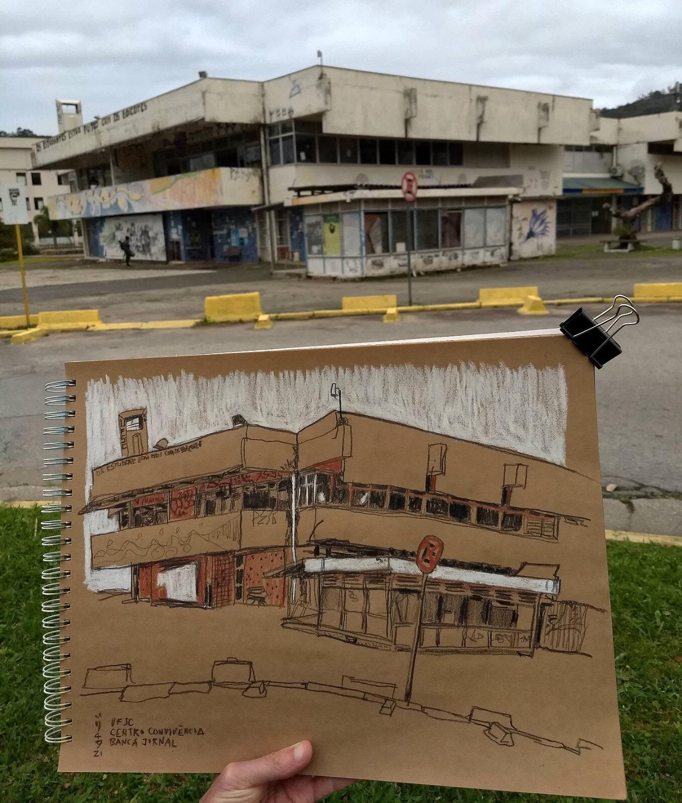 Foto do caderno com o desenho do Centro de Convivência em primeiro plano tendo ao fundo o Centro e a banca de jornais