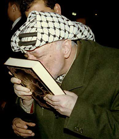 Arafat kisses the Koran. Its a matter of pride for his god to take back Palestine